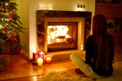 Young woman by a fireplace on Christmas Stock Photo