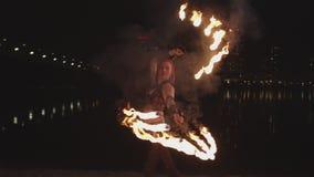 Pretty firegirl performing art of spinning fans stock video footage