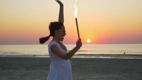 Young woman with a firework candle in her hand jumping happily on the beach stock video