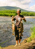 The  young woman  with the fish. On the river bank, Kamchatka Stock Images