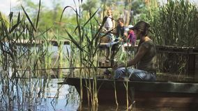 Young woman fisherman is fishing on the forest lake, holding the fishing rod twists the coil. stock video footage