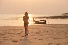 Panoramic view of Young asian woman and Fishing boat on the beach in sunset. Young woman and Fishing boat in sunset on tropical beach stock image