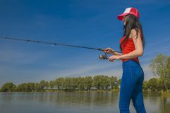 Fishing. Young sexy woman catches fish by spinning rod at lake in summer.  royalty free stock photos