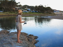 Young woman fishing at river by dusk Stock Photo