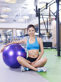 Young woman with fitness ball. Young woman sitting next to a fitness ball Stock Images