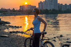Woman with a fitness bracelet stands and rests after a bike ride Stock Photos