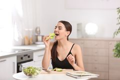 Young woman in fitness clothes eating lettuce while preparing healthy breakfast. At home royalty free stock photo