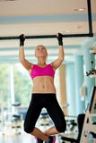 Young woman in fitness gym lifting on bar Stock Photography