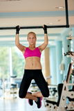 Young woman in fitness gym lifting on bar Royalty Free Stock Image