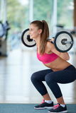 Young woman in fitness gym lifting  weights Royalty Free Stock Images