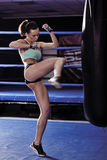 Young woman fitness kicking in front of punching bag Stock Image