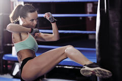 Young woman fitness kicking in front of punching bag Stock Images