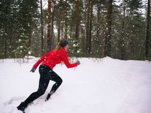 Young woman fitness model running in a city park. Runner jogging in snow. royalty free stock images
