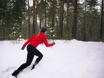 Young woman fitness model running in a city park. Runner jogging in snow. Stock Photography