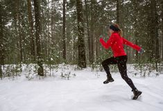 Young woman fitness model running in a city park. Winter running exercise. Stock Image
