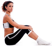 Young woman in fitness sitting on the floor stock image