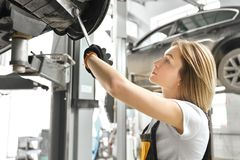 Free Young Woman Fixing Car Undercarriage In Autoservice. Royalty Free Stock Image - 142864296