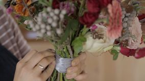 Young woman is fixing satin ribbon on floral bouquet indoors. stock footage