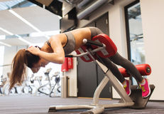 Young woman flexing back muscles on bench in gym. Sport, training, fitness, lifestyle and people concept - young woman flexing back and abdominal muscles on royalty free stock photography