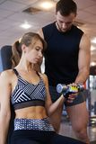 Young woman flexing biceps with personal trainer at gym stock photography