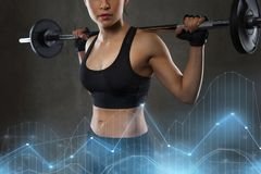 Young woman flexing muscles with barbell in gym Royalty Free Stock Images