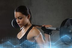 Young woman flexing muscles with barbell in gym Royalty Free Stock Photos