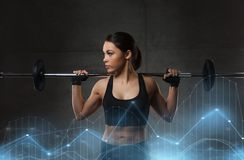 Young woman flexing muscles with barbell in gym Royalty Free Stock Photo