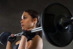 Young woman flexing muscles with barbell in gym Stock Photography