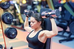 Young woman flexing muscles with dumbbell in gym Stock Image