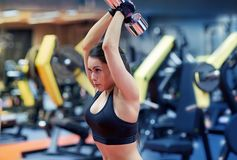 Young woman flexing muscles with dumbbell in gym Royalty Free Stock Images