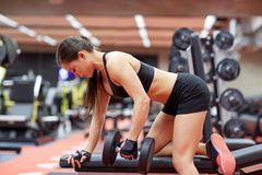 Young woman flexing muscles with dumbbell in gym. Sport, fitness, bodybuilding, weightlifting and people concept - young woman with dumbbell flexing muscles in Royalty Free Stock Photos