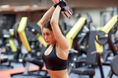 Young woman flexing muscles with dumbbell in gym. Sport, fitness, bodybuilding, weightlifting and people concept - young woman with dumbbell flexing muscles in Stock Photo