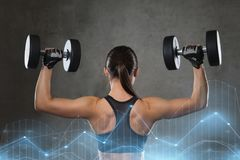 Young woman flexing muscles with dumbbells in gym Stock Photography