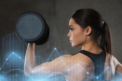Young woman flexing muscles with dumbbells in gym Royalty Free Stock Photos