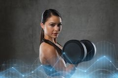 Young woman flexing muscles with dumbbells in gym Royalty Free Stock Image