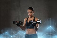 Young woman flexing muscles with dumbbells in gym Stock Image