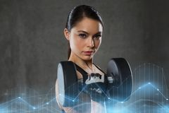 Young woman flexing muscles with dumbbells in gym Royalty Free Stock Photo