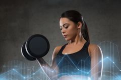 Young woman flexing muscles with dumbbells in gym Stock Images