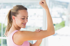 Young woman flexing muscles in the gym Stock Photos