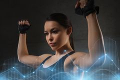 Young woman flexing muscles in gym. Sport, fitness, bodybuilding, weightlifting and people concept - young woman flexing muscles in gym Royalty Free Stock Images