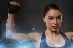 Young woman flexing muscles in gym Royalty Free Stock Image