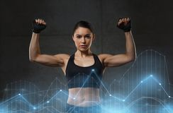 Young woman flexing muscles in gym Stock Images