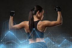 Young woman flexing muscles in gym Royalty Free Stock Photography