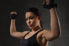 Young woman flexing muscles in gym. Sport, fitness, bodybuilding, weightlifting and people concept - young woman flexing muscles in gym Stock Photography