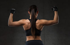 Young woman flexing muscles in gym. Sport, fitness, bodybuilding, weightlifting and people concept - young woman flexing muscles in gym Royalty Free Stock Photos