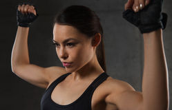Young woman flexing muscles in gym. Sport, fitness, bodybuilding, weightlifting and people concept - young woman flexing muscles in gym Royalty Free Stock Image