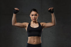 Young woman flexing muscles in gym. Sport, fitness, bodybuilding, weightlifting and people concept - young woman flexing muscles in gym Stock Photo