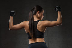 Young woman flexing muscles in gym. Sport, fitness, bodybuilding, weightlifting and people concept - young woman flexing muscles in gym Royalty Free Stock Photography