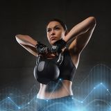 Young woman flexing muscles with kettlebell in gym. Fitness, sport, exercising, weightlifting and people concept - young woman flexing muscles with kettlebell in Royalty Free Stock Photography