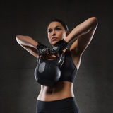 Young woman flexing muscles with kettlebell in gym Royalty Free Stock Images